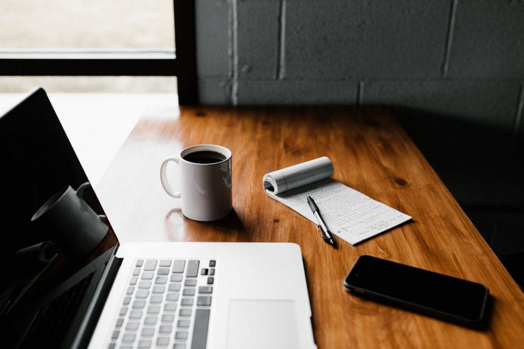 Ordinateur avec un bloc note, un téléphone et une tasse posé sur un bureau en bois