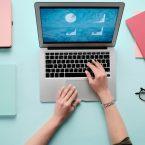 Image colorée avec une personne travaillant sur son Macbook de Apple et avec des carnets de notes