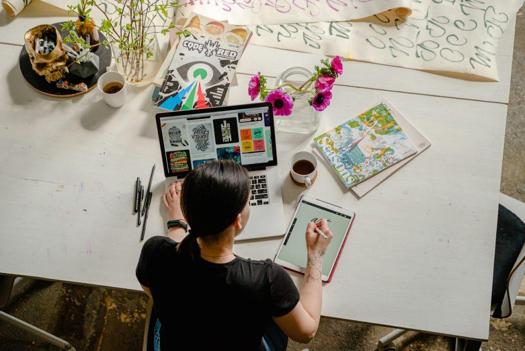 Femme créative travaillant sur sa tablette et pc